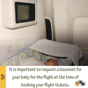 Baby in aeroplane bassinet with tip on the importance of booking bassinet at time of booking long distance fights.
